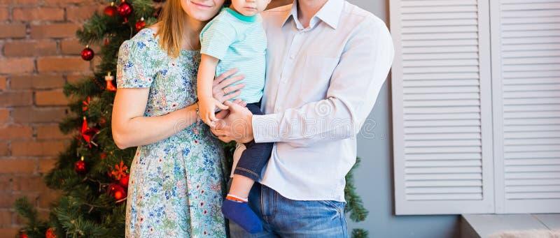 Famiglia di Natale con il bambino Genitori felici e bambini sorridenti a casa che celebrano nuovo anno Albero di Natale fotografia stock