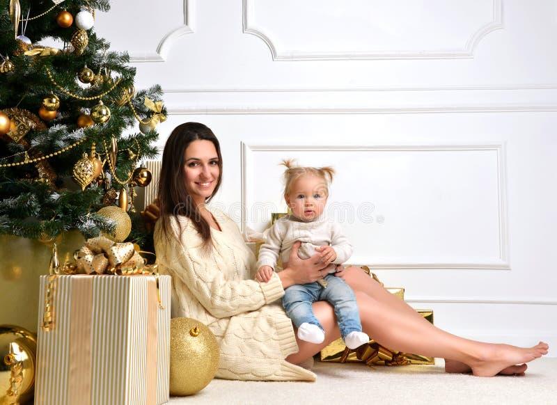 Famiglia di Natale con la donna della madre con la ragazza del bambino del bambino e l'oro c fotografie stock libere da diritti