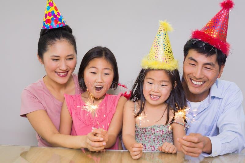 Famiglia di quattro allegra che gioca con i petardi fotografia stock
