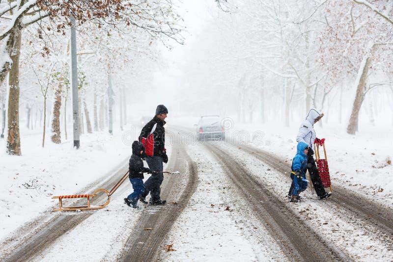 Famiglia di quattro che attraversa con attenzione la via coperta di neve e di fango fotografia stock