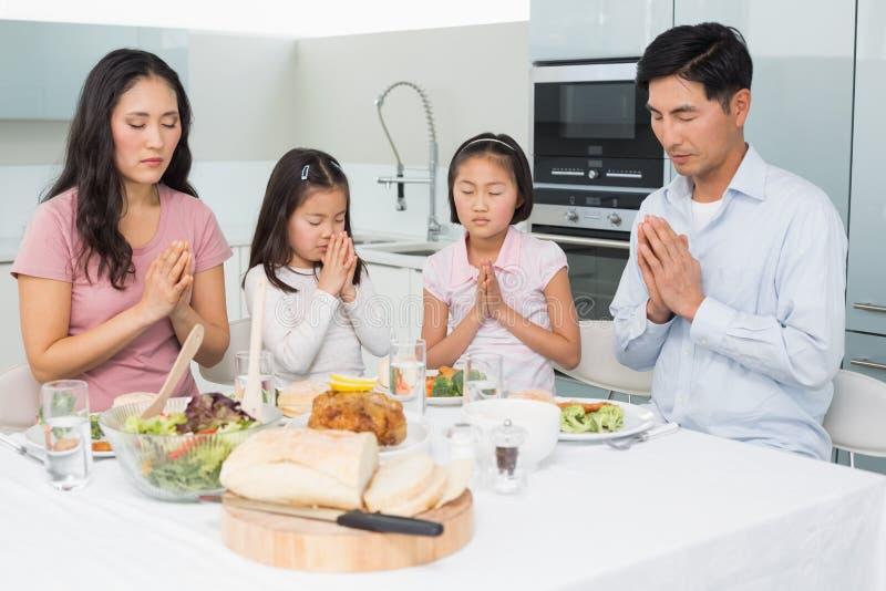 Famiglia di quattro che dice tolleranza prima del pasto in cucina fotografia stock