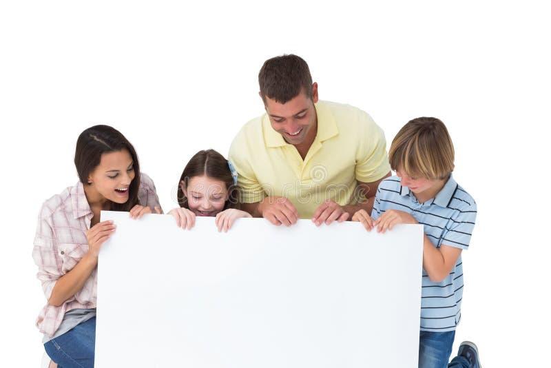Famiglia di quattro che esamina tabellone per le affissioni fotografia stock