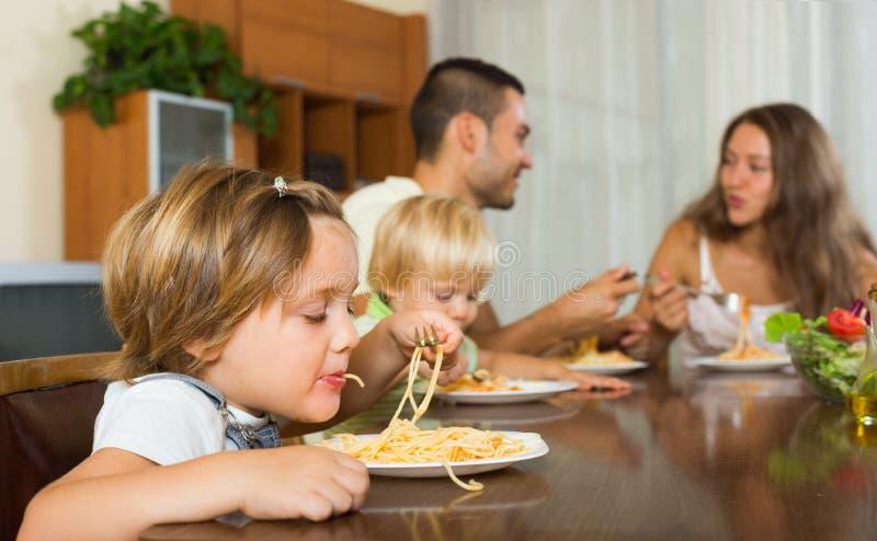 Famiglia di quattro che mangia gli spaghetti immagini stock libere da diritti