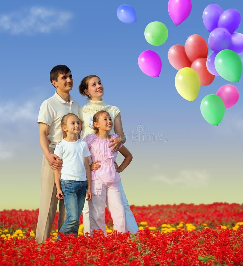 Famiglia di quattro in collage rosso degli aerostati e del campo fotografia stock libera da diritti