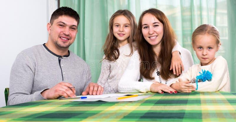 Famiglia di quattro felice che firma i documenti immagini stock libere da diritti