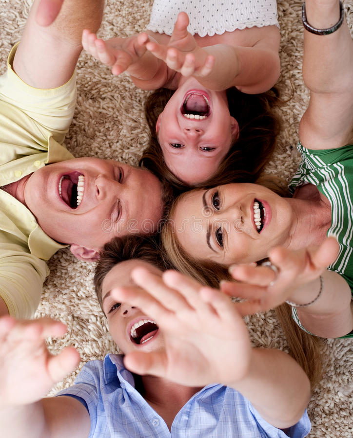 Famiglia di quattro felice che si trova sulla moquette fotografia stock libera da diritti