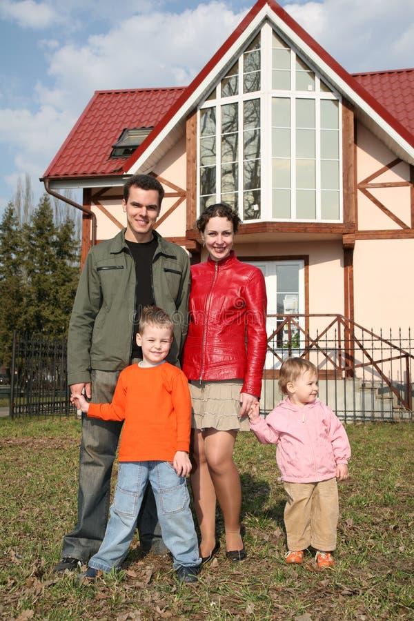 Famiglia di quattro vicino alla casa fotografie stock