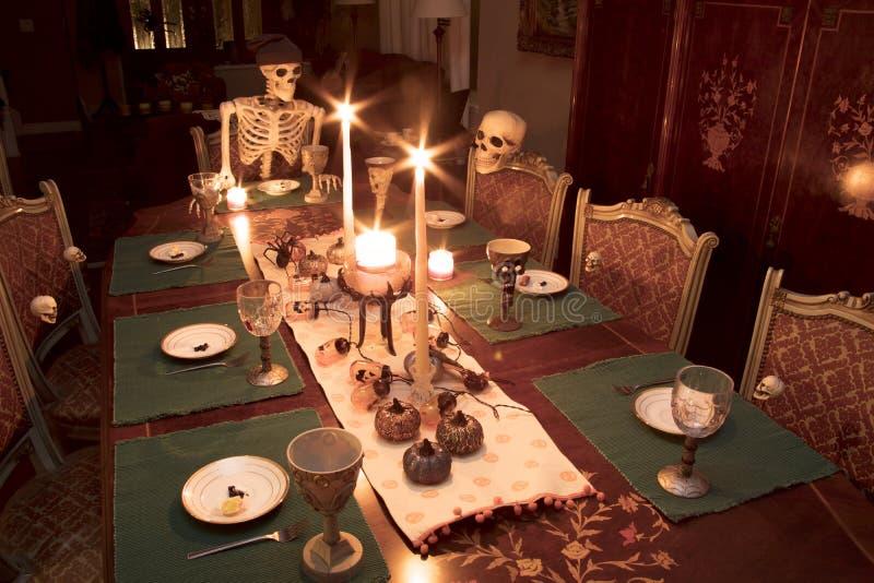 Famiglia di scheletro di Halloween che celebra una cena di festa immagini stock