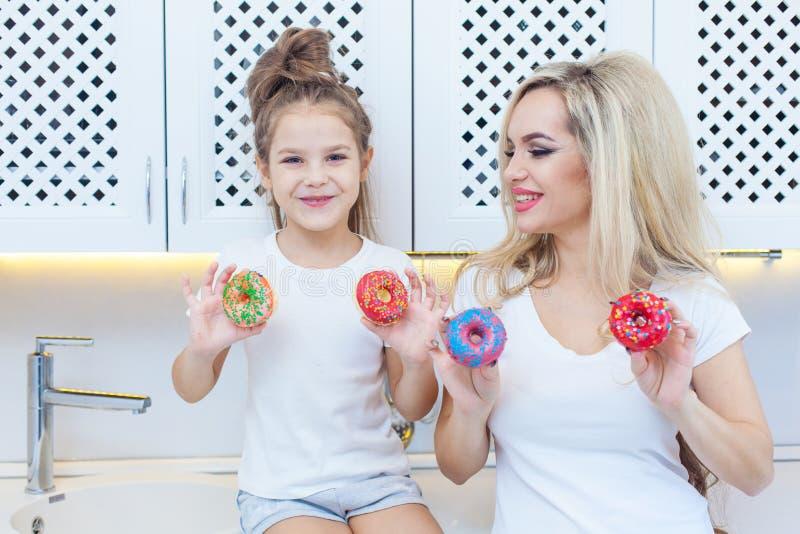 Famiglia divertente sui precedenti della cucina luminosa La madre e la sua ragazza della figlia stanno divertendo con le guarnizi immagini stock