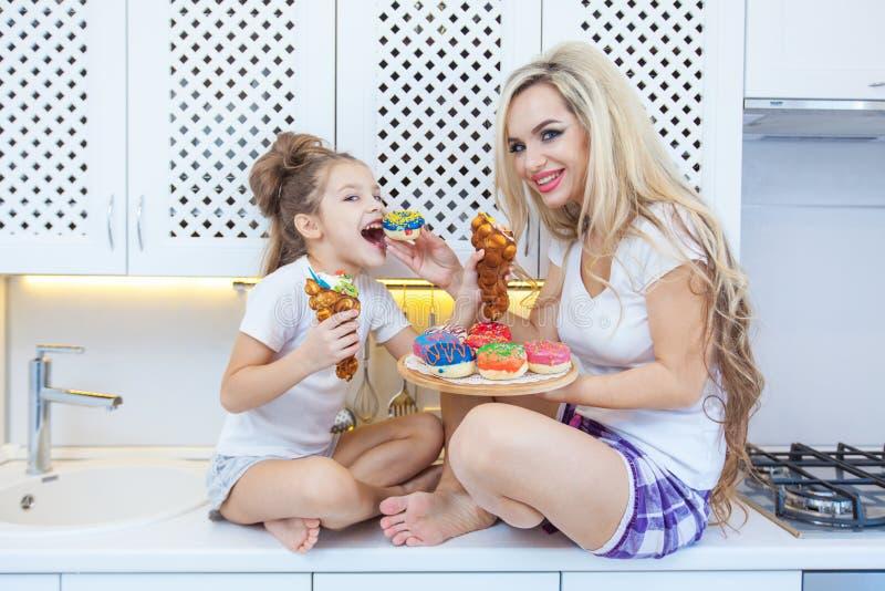 Famiglia divertente sui precedenti della cucina luminosa La madre e la sua ragazza della figlia stanno divertendo con le guarnizi immagine stock libera da diritti