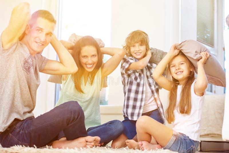 Famiglia e bambini che hanno lotta di cuscino immagine stock