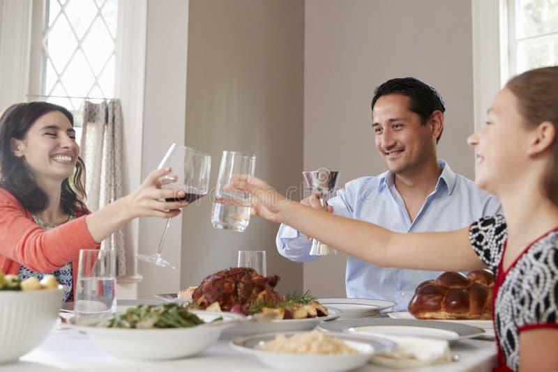 Famiglia ebrea che alza i vetri alla tavola per il pasto di Shabbat fotografie stock