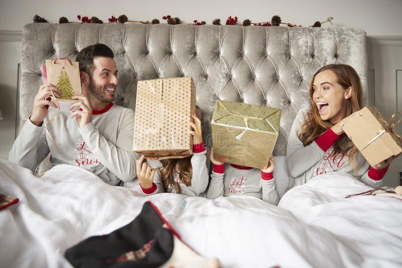 Famiglia emozionante a letto a casa che scuote i contenitori di regalo sul giorno di Natale immagine stock