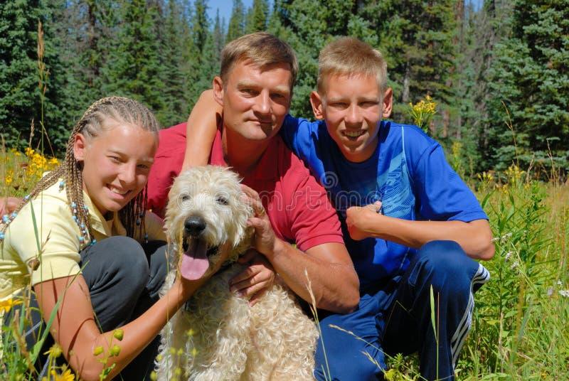 Famiglia esterna con il cane fotografia stock libera da diritti