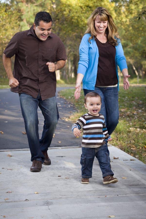Famiglia etnica felice della corsa Mixed che cammina nella sosta fotografia stock