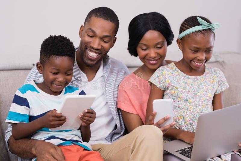 Famiglia facendo uso delle tecnologie mentre sedendosi sul sofà a casa fotografie stock libere da diritti