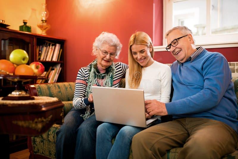 Famiglia facendo uso di un computer che si siede sullo strato e che ha smilin felice immagine stock
