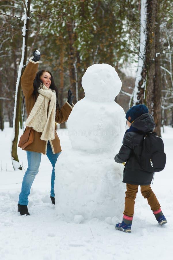 Famiglia felice in abbigliamento caldo Palle di neve sorridenti del gioco del figlio e della madre accanto ad un pupazzo di neve  immagine stock