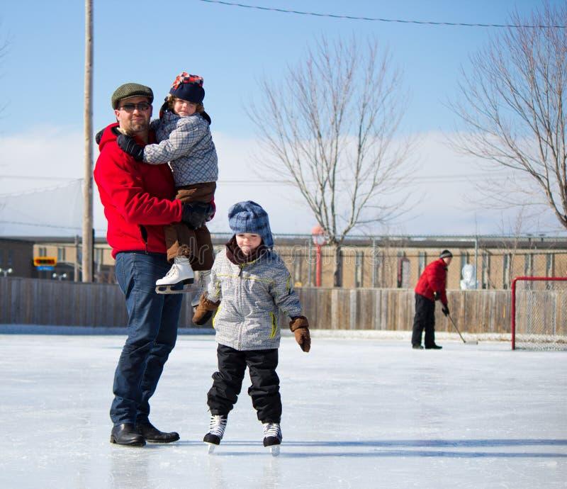 Famiglia felice alla pista di pattinaggio pattinante immagine stock