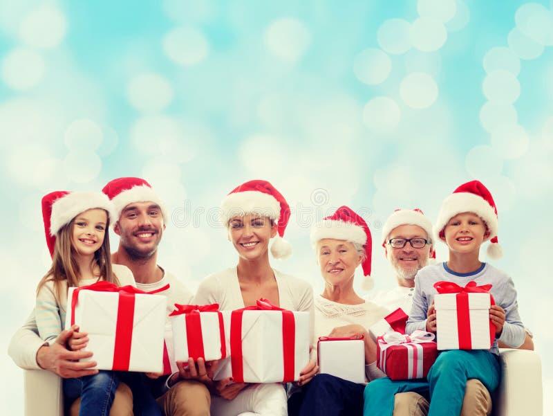 Famiglia felice in cappelli dell'assistente di Santa con i contenitori di regalo fotografie stock libere da diritti