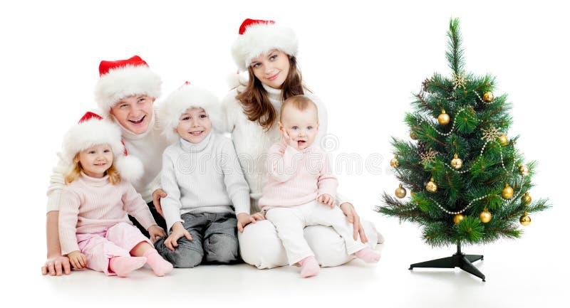 Famiglia felice in cappelli della Santa con l'albero di Natale fotografie stock libere da diritti
