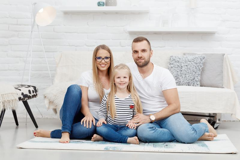 Famiglia felice a casa che si siede sul pavimento immagine stock libera da diritti
