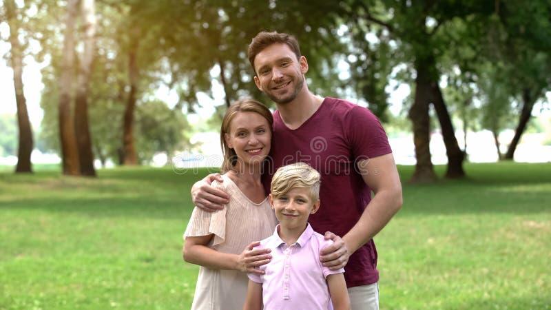 Famiglia felice che abbraccia e che esamina macchina fotografica, assicurazione sociale, protezione fotografia stock