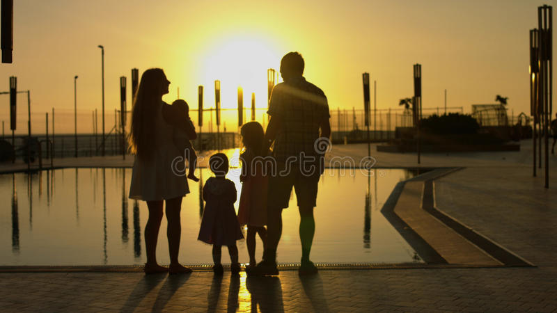 Famiglia felice che ammira il tramonto dallo stagno fotografia stock