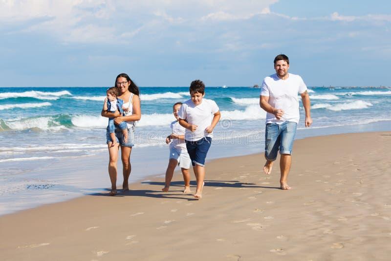 Famiglia felice che cammina sulla spiaggia immagini stock