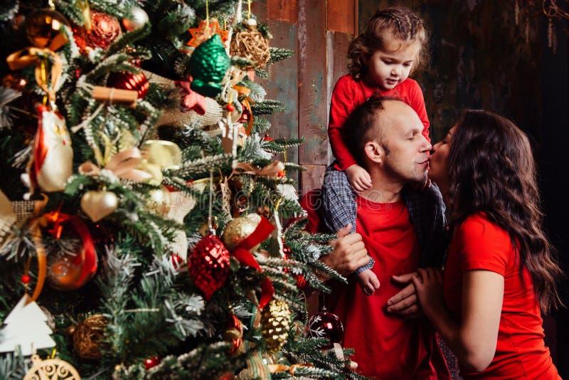 Famiglia felice che decora un albero di Natale con i boubles nel salone fotografie stock libere da diritti