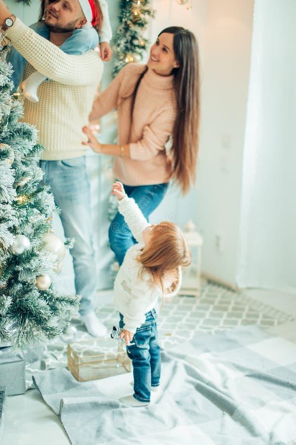 Famiglia felice che decora un albero di Natale con i boubles nel salone fotografia stock libera da diritti