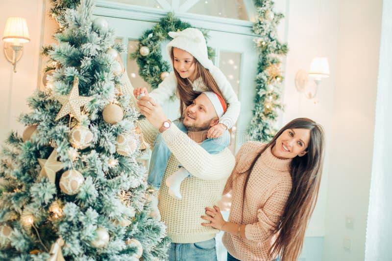 Famiglia felice che decora un albero di Natale con i boubles nel salone fotografie stock