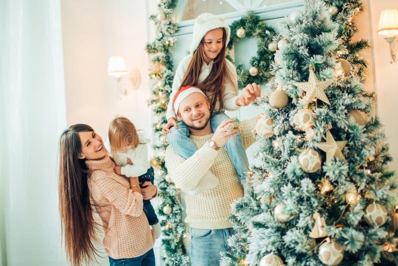 Famiglia felice che decora un albero di Natale con i boubles nel salone immagini stock libere da diritti