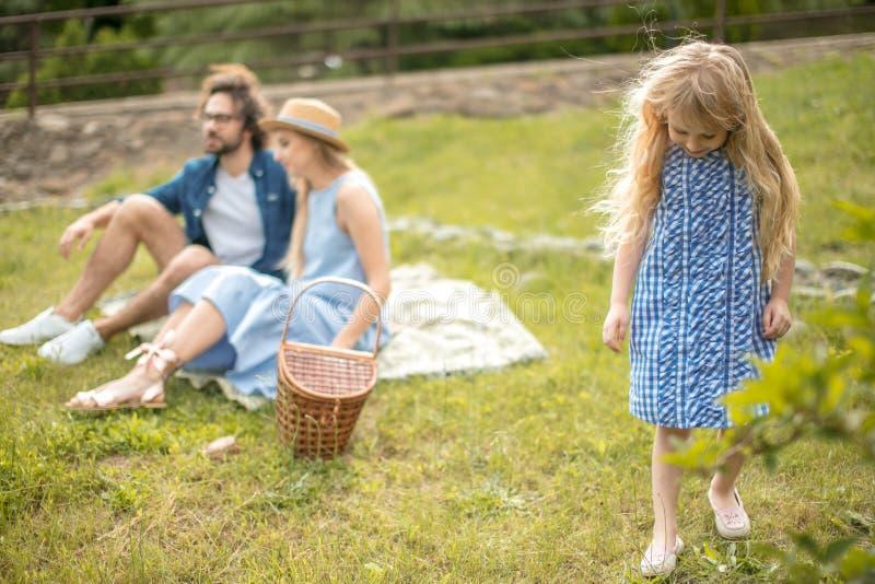 Famiglia felice che fa un picnic all'aperto con la loro figlia sveglia, vestiti blu, donna in cappello fotografia stock libera da diritti