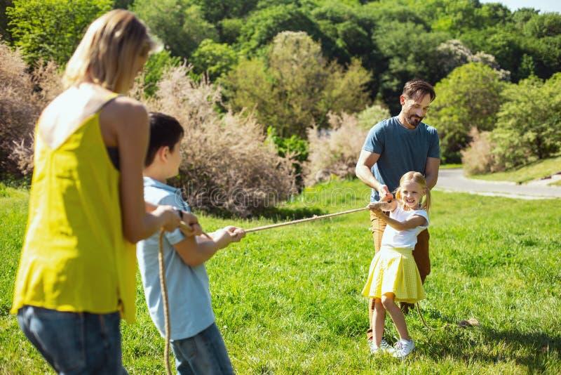 Famiglia felice che gioca nel parco immagine stock
