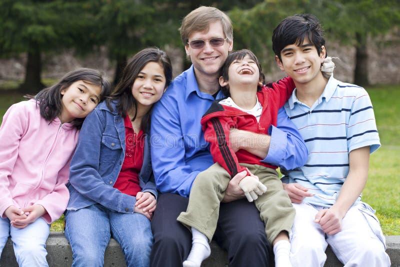 Famiglia felice che gode del giorno alla sosta fotografia stock