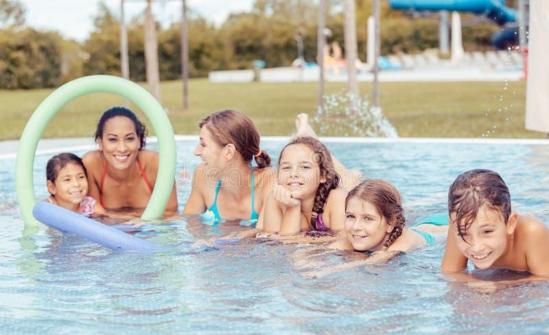 Famiglia felice che gode nella piscina fotografie stock