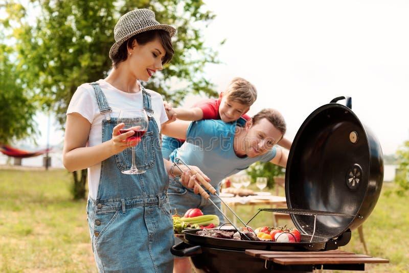 Famiglia felice che ha barbecue con la griglia moderna immagini stock libere da diritti