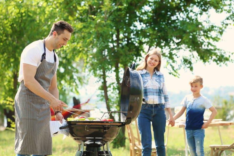 Famiglia felice che ha barbecue con la griglia moderna all'aperto immagine stock libera da diritti