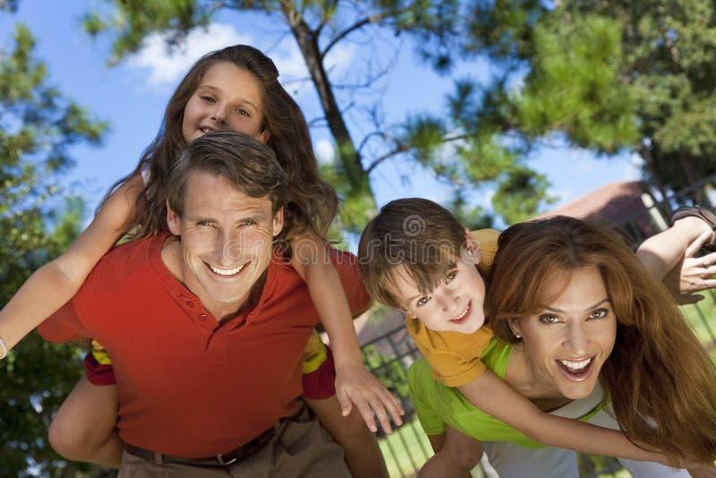 Famiglia felice che ha divertimento all'esterno in sosta immagine stock