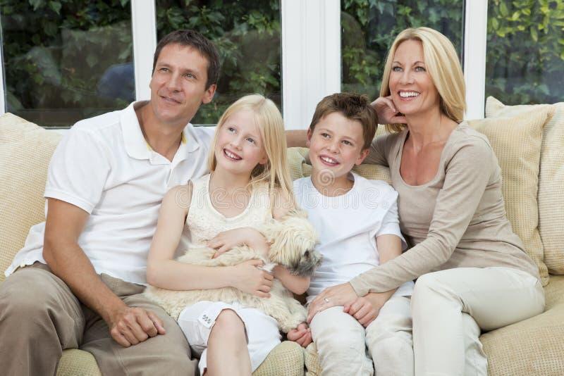Famiglia felice che ha divertimento sedersi con il cane di animale domestico immagini stock libere da diritti