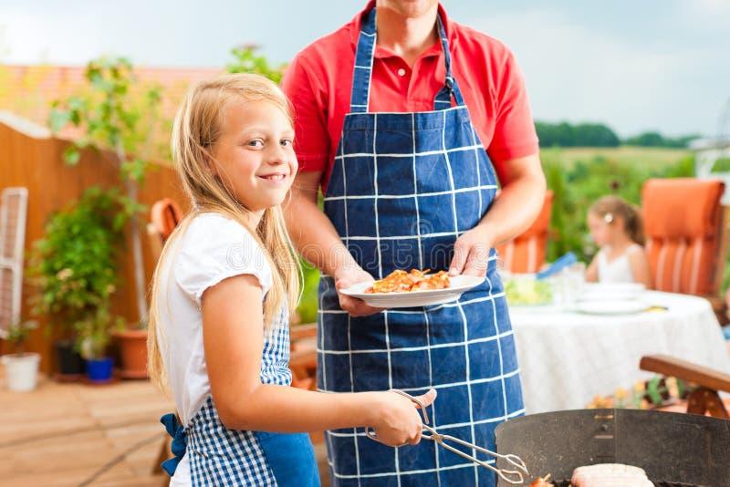 Famiglia felice che ha un barbecue fotografia stock