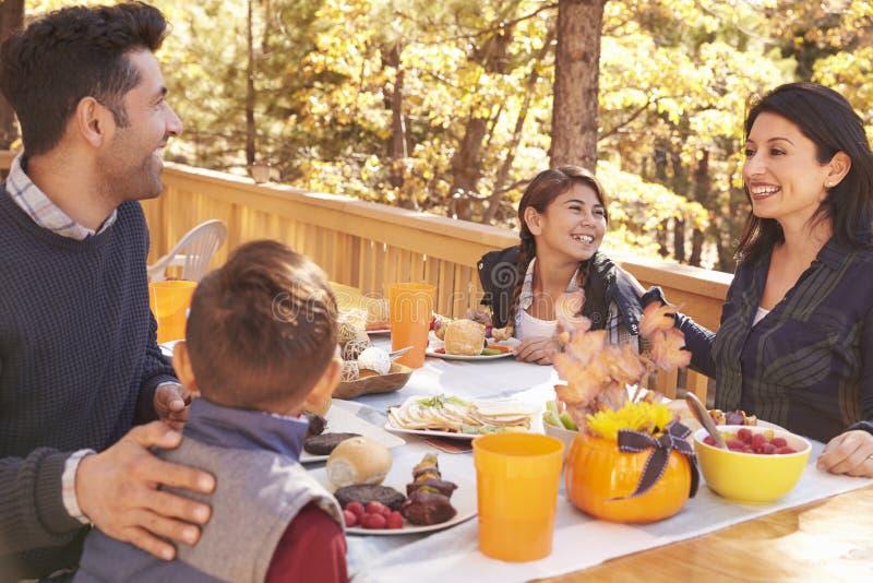 Famiglia felice che mangia alla tavola su una piattaforma in una foresta fotografia stock libera da diritti