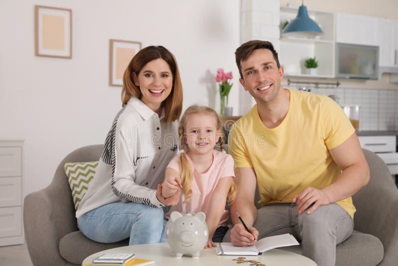 Famiglia felice che mette moneta nel porcellino salvadanaio alla tavola Soldi di risparmio immagini stock