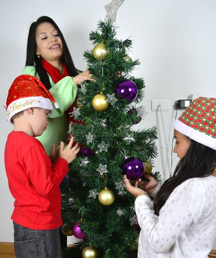 Famiglia felice che pone sotto l'albero di Natale fotografie stock