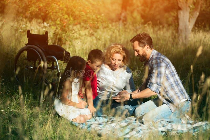 Famiglia felice che prende selfie sul picnic in parco paraplegic immagine stock libera da diritti