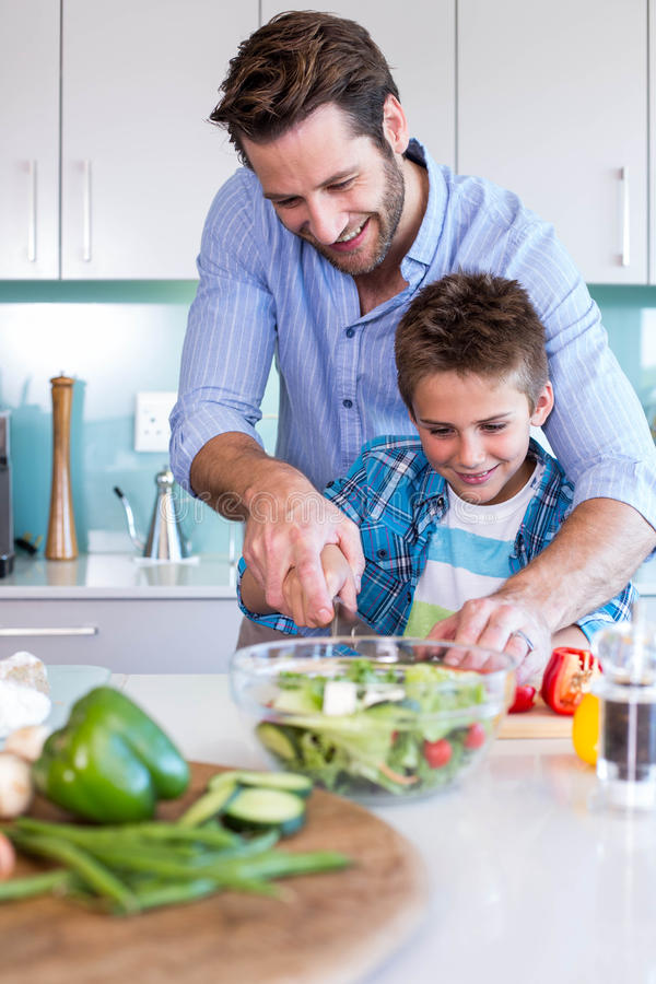 Famiglia felice che prepara insieme le verdure immagine stock