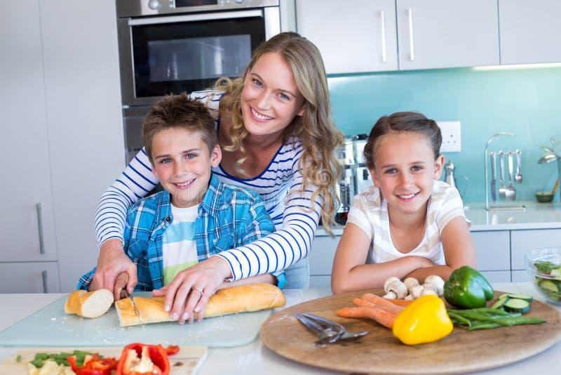 Famiglia felice che prepara insieme pranzo immagine stock