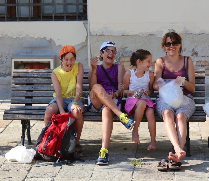 Famiglia felice che ride sul banco che fa i picnic fotografie stock libere da diritti