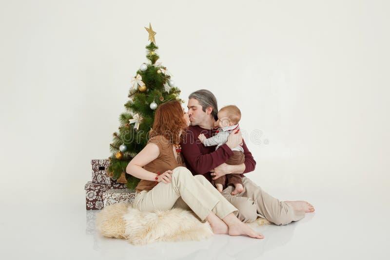 Famiglia felice che si siede all'albero del nuovo anno sullo studio bianco immagine stock